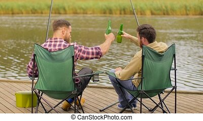 happy friends fishing and drinking beer on lake - leisure...