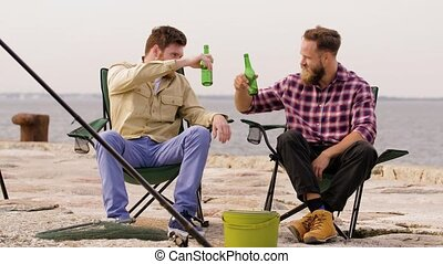happy friends fishing and drinking beer on pier - leisure...