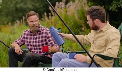 friends fishing and drinking tea from thermos - leisure and...