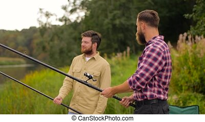 happy friends with fishing rods on lake - leisure and people...