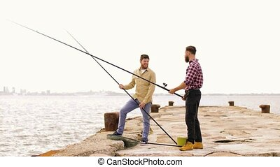 happy friends with fishing rods on pier - leisure and people...