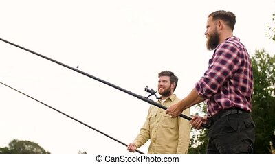 happy friends with fishing rods - leisure and people concept...