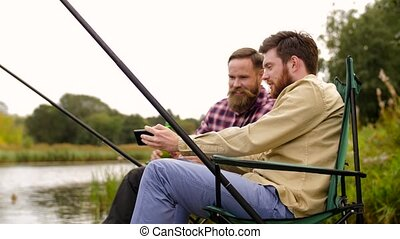 friends with smartphone and beer fishing on lake - leisure...