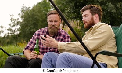 friends with smartphone fishing and drinking beer - leisure...