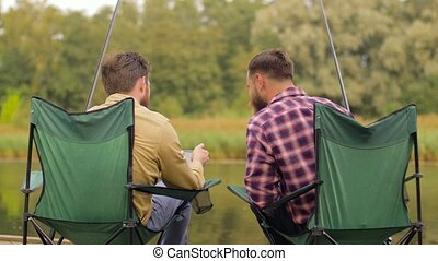 friends with smartphone fishing on lake - leisure and people...