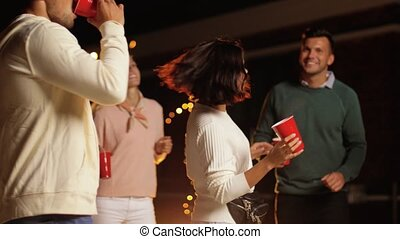 friends with drinks dancing at rooftop party - leisure,...