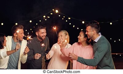 happy friends with sparklers at rooftop party - leisure,...