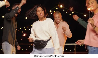 friends with sparklers dancing at rooftop party - leisure,...