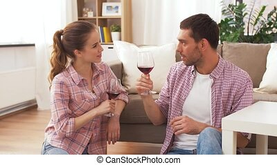happy couple drinking red wine at home - leisure,...