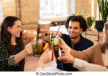 happy friends clinking drinks at bar or cafe