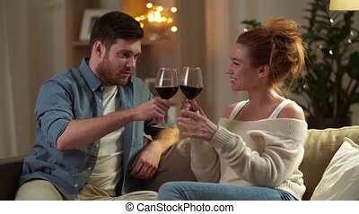 happy couple drinking red wine at home in evening - leisure,...