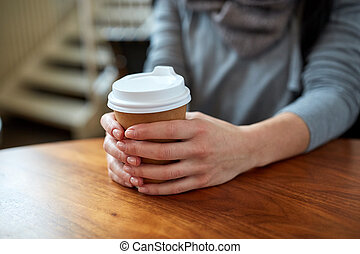smiling young woman drinking coffee at cafe