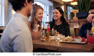 happy friends eating and drinking at bar or cafe