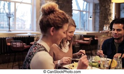 happy friends eating and drinking at restaurant