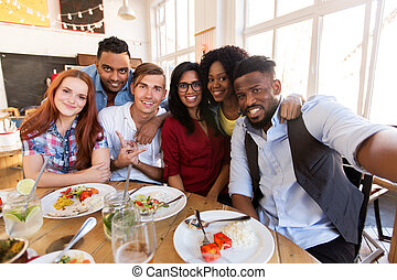 happy friends taking selfie at restaurant or bar