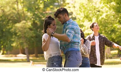 happy friends dancing at summer party in park