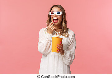 Leisure, going-out and spring concept. Portrait of attractive young woman in white dress enjoying watching interesting movie on full screen at cinema, eating popcorn and wearing 3d glasses