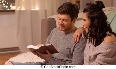 happy couple reading book at home - leisure, hygge and...