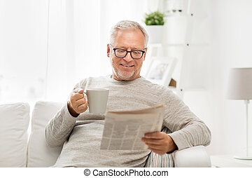 senior man in glasses reading newspaper at home - leisure,...