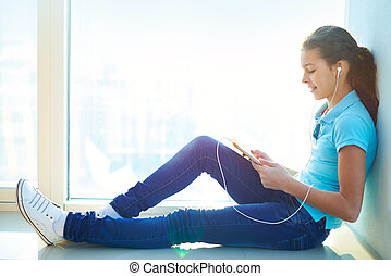 Leisure moment - Lovely girl listening to the music during...