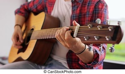 leisure, music and people concept - young man playing guitar sitting on windowsill