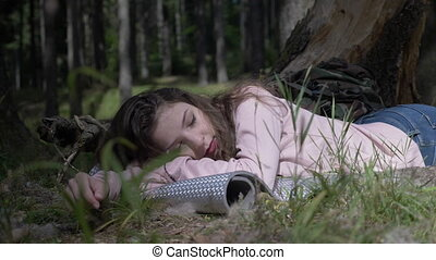 Leisure of the beautiful camping girl lying down and chilling on the grass deep in the forest
