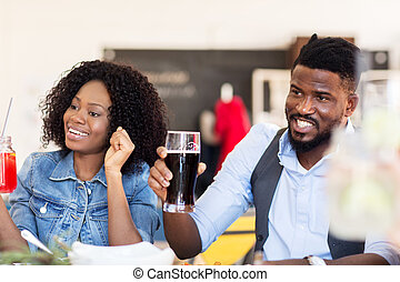 happy african american couple with drinks at bar