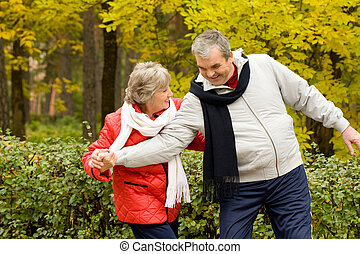 Leisure - Photo of two aged people having fun during walk in...