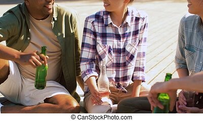 friends drinking beer and cider on wooden terrace - leisure,...