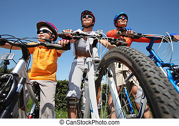Leisure - Portrait of happy family on bicycles against blue...