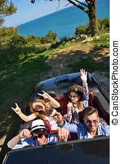 leisure, road trip, travel and people concept - happy friends driving in cabriolet car along country road