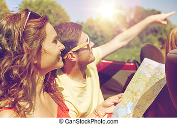happy friends with map driving in cabriolet car