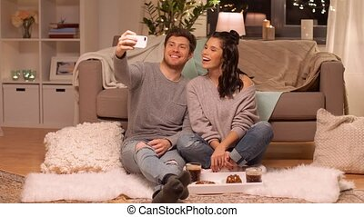 happy couple taking selfie by smartphone at home - leisure,...