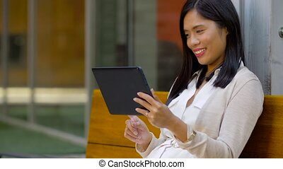 asian woman with tablet computer sitting on bench - leisure,...