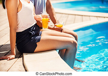 Leisure time poolside. Close-up of couple in casual wear...