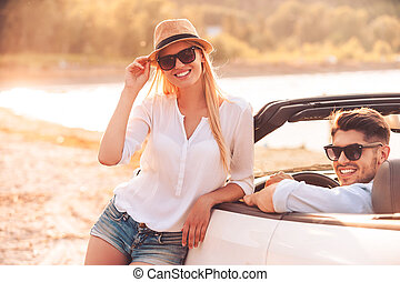 Leisure time we are spending together. Happy young woman leaning at white convertible while her boyfriend sitting on the front seat of it
