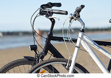 close up of two bicycles on beach