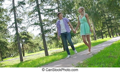 Leisure Walk - Slow motion of sweethearts striding along the...