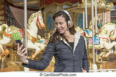 leisure, woman next to a merry-go-round taking selfie with the cell phone on a spring afternoon. image of freshness and lifestyle in europe