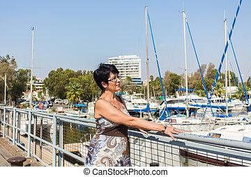 Leisure woman on holiday near yacht and sailboats marina resort town. Luxury lifestyle.