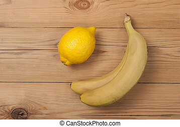 Lemon and bananas on a wooden background.