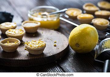 Lemon and custard mini tarts on wooden board