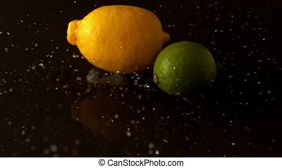 Lemon and lime dropping on wet black surface in slow motion