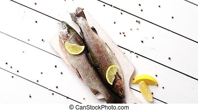 Lemon and pepper around fish - From above shot of slices of...