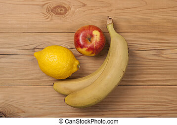 Lemon apple and bananas on a wooden background.