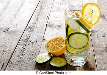 Lemon cucumber detox water in a glass with slices against a rustic wood background