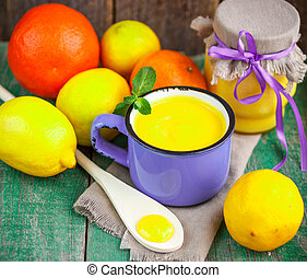 Lemon custard and fresh lemons, oranges and mint on old...