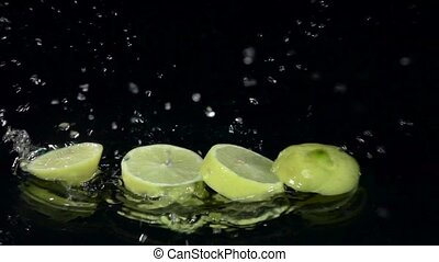 Lemon dissolves into slices when it falls into the water. Black background. Slow motion