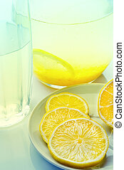 lemon drink in a jug and glass, lies next to a lemon