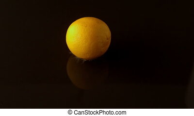 Lemon dropping on wet black surface in slow motion